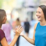 Two happy friends greeting and meeting on the street -shutterstock_721187443 copy