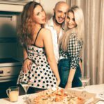 One man with two beautiful girls at home pizza party laughing. – shutterstock_373861729