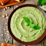 Basil pesto hummus on a dark wood background. the toning. selective focus